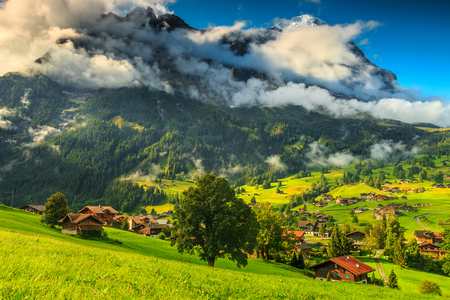 eiger: Green fields and famous touristic town with high North Face of Eiger mountains,Bernese Oberland,Switzerland,Europe Stock Photo
