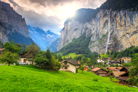 Green fields and famous touristic town with high waterfall in background,Lauterbrunnen,Bernese Oberland,Switzerland,Europe Stock Photo