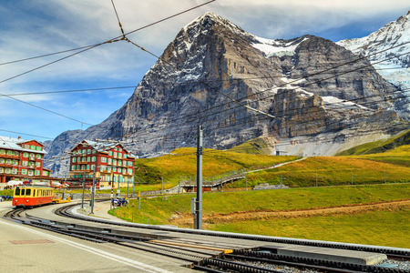 eiger: Famous electric red tourist train and Kleine Scheidegg train station with Eiger North Face in background,Bernese Oberland,Switzerland,Europe Stock Photo