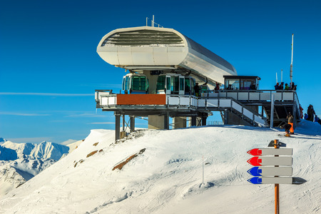 station ski: Ski resort with cable car station and ski course signboard in the French Alps,Les Menuires,3 Vallee,France,Europe
