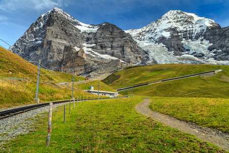 the bernese oberland: Famous electric railroad near Kleine Scheidegg train station with Eiger North Face in background,Bernese Oberland,Switzerland,Europe