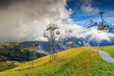 the bernese oberland: Stunning alpine landscape and green fields with cableway near First station,Schreckhorn mountains in background,Grindelwald,Bernese Oberland,Switzerland,Europe Stock Photo