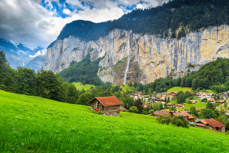 the bernese oberland: Green fields and famous touristic town with high waterfall in background,Lauterbrunnen,Bernese Oberland,Switzerland,Europe Stock Photo