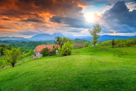 spring landscape: Spring landscape with stunning colorful sunset and Piatra Craiului mountains in background,Transylvania,Romania,Europe