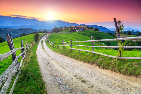 Spring alpine landscape with green fields and majestic sunset