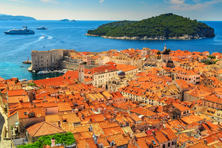 mediterranean houses: Traditional Mediterranean houses with red tiled roofs and rocky green idyllic island in background,Dubrovnik,Dalmatia,Croatia,Europe
