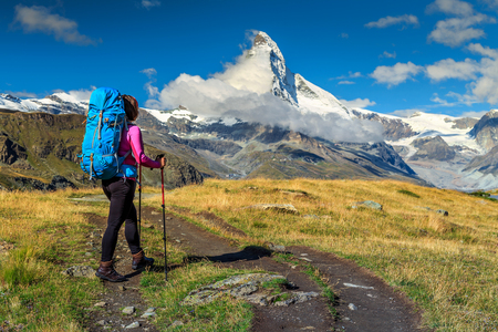 valais: Hiker woman with backpack and mountain equipment,looking at view in Valais region,Matterhorn,Switzerland,Europe Stock Photo