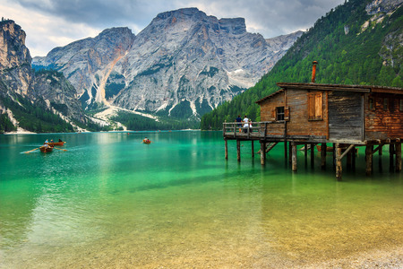 fishing huts: Old wooden dock house on the lake with typical wooden boats,Braies lake,Dolomites,Italy,Europe Stock Photo