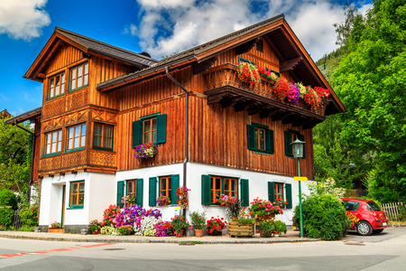 chalets: Typical alpine wooden house with colorful flowers on balcony,Austria,Europe