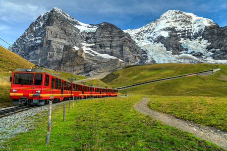 the bernese oberland: Famous electric red tourist train coming down from the Jungfraujoch station(top of Europe) in Kleine Scheidegg,Bernese Oberland,Switzerland,Europe