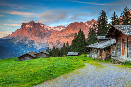Beautiful alpine landscape,old Swiss traditional wooden hut and magical sunset with Wetterhorn peak in background,Grindelwald,Bernese Oberland,Switzerland,Europe