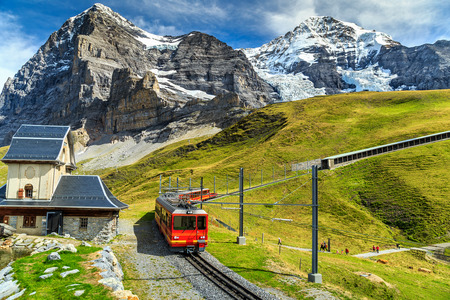 railway: Famous electric red tourist train coming down from the Jungfraujoch station(top of Europe) in Kleine Scheidegg,Bernese Oberland,Switzerland,Europe
