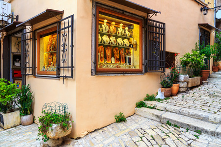 paved: Stunning jewelry store in old medieval paved street with mediterranean colorful flowers in the entrance Stock Photo