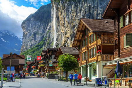 chalets: Spectacular principal street of Lauterbrunnen with shops,hotels,terraces,swiss flags and stunning Staubbach waterfall in background,Bernese Oberland,Switzerland,Europe Editorial