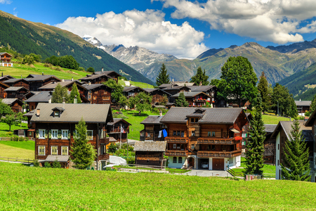 the bernese oberland: Green fields and famous typical Swiss village with traditional wooden houses,Bernese Oberland,Switzerland,Europe