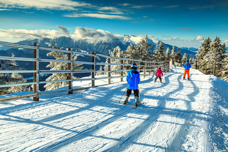 Stunning winter landscape with wonderful Bucegi mountains in background and skiers on the ski slopes,Poiana Brasov ski resort,Transylvania,Romania,Europe Standard-Bild