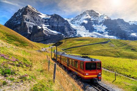 Beroemde elektrische rode toeristische trein naar beneden van het Jungfraujoch station (top van Europa) in Kleine Scheidegg, Berner Oberland, Zwitserland, Europa