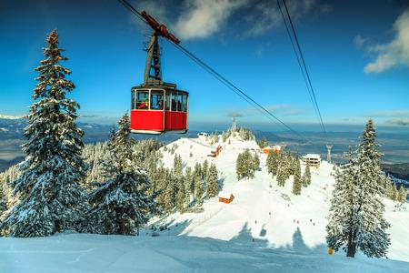 Red cable car moving down in Poiana Brasov famous ski resort,Carpathians,Transylvania,Romania,Europe
