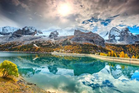 yellow trees: Fantastic autumn landscape,alpine lake and yellow pine trees,Fedaia lake with famous Marmolada peak in background,Dolomites,Italy,Europe