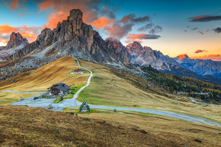 Fantastic autumn landscape,alpine pass and yellow pine trees,Passo Giau with famous Ra Gusela,Nuvolau peaks in background,Dolomites,Italy,Europe