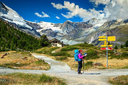 mapa de europa: paisaje alpino impresionante, caminante de la mujer con mochila, mapa en papel, orientar y encontrar dirección en la alta montaña, Zermatt, Valais, Suiza, Europa