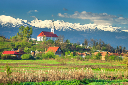 plowing: Amazing spring countryside landscape with church of Mandra and high snowy Fagaras mountains in background, Brasov region, Transylvania, Romania, Europe