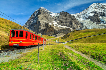 Famous electric retro red tourist train coming down from the Jungfraujoch station(top of Europe) in Kleine Scheidegg, Bernese Oberland, Switzerland, Europe