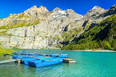 Amazing alpine lake and stunning mountains with blue boats, Oeschinen lake, Bernese Oberland, Switzerland, Europe