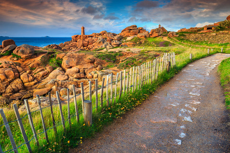 Amazing sunset with lighthouse of Ploumanach Mean Ruz in Perros-Guirec on Pink Granite Coast and spectacular walkway near ocean, Brittany, France, Europe
