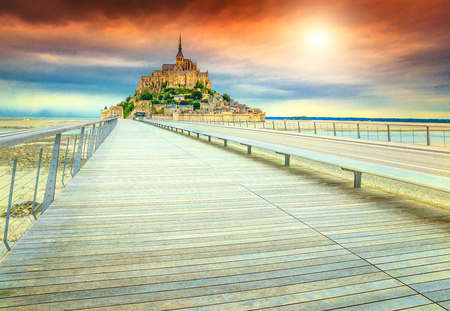 heritage protection: Magical colorful sunset and fabulous Mont Saint Michel cathedral on the island with modern bridge, Normandy, Northern France, Europe