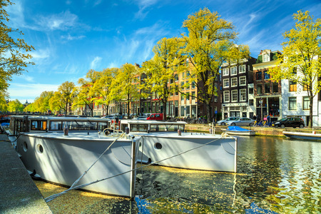 dutch typical: Famous Amsterdam canals with boats and typical dutch houses in capital of Netherlands, Europe