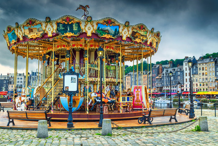 Spectacular retro carousel in the city. Merry-go-round with horses and landau in the famous French harbour, Honfleur, Normandy, France, Europe