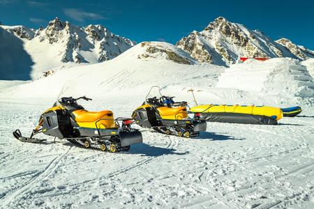 Fantastic winter landscape with yellow snowmobiles in the famous Fagaras mountains near frozen Balea lake, Carpathians, Transylvania, Romania, Europe Stock Photo