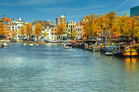 Amazing Amsterdam canals with boats and typical dutch houses in capital of Netherlands, Europe