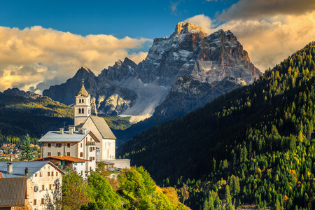 Fantastic alpine spring landscape with church on the Santa Lucia pass and Pelmo mountain group in background, Colle Santa Lucia, Dolomites, Italy, Europe Stock Photo