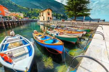 Amazing fishing harbor with colorful boats on the clean mountain lake, Garda lake, Torbole holiday resort, Trentino Alto Adige region, Italy Stock Photo