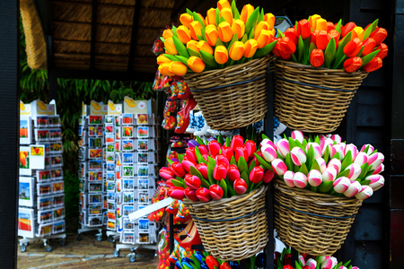 Breathtaking colorful bouquets of wooden tulips in the basket, wooden shoes on shelf and spectacular colorful postcards. Dutch souvenir shop decoration in Amsterdam, Netherlands, Europe  Stock Photo