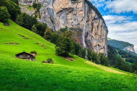 Fattoria rurale svizzera con pascolo, campi verdi estivi e alta cascata di Staubbach in background, città turistica di Lauterbrunnen, regione dell'Oberland bernese, Svizzera, Europa