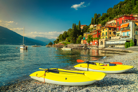 Stunning holiday resort, luxury colorful villas and harbor with kayaks, luxury yachts, motorboats in Varenna, Lake Como, Lombardy region, Italy, Europe