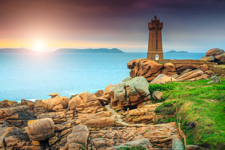 Breathtaking sunset with lighthouse of Ploumanach Mean Ruz in Perros-Guirec on Pink Granite Coast, Brittany, France, Europe