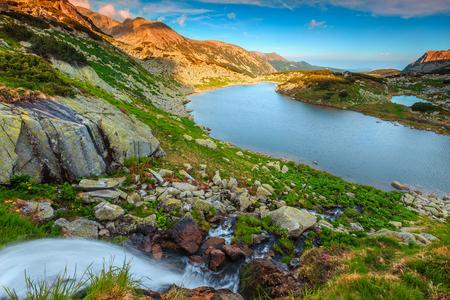 Majestic summer landscape, spectacular waterfall with alpine glacier lake, Retezat mountains, Carpathians, Transylvania, Romania, Europe
