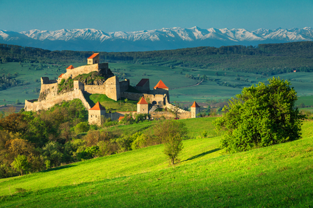 Famous Rupea fortress, spectacular fortification and high snowy mountains in background, Brasov, Transylvania, Romania, Europe