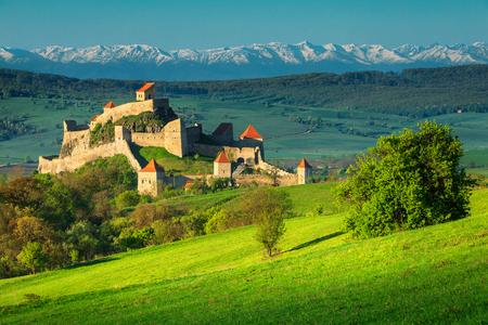 La famosa fortaleza de Rupea, espectacular fortificación y altas montañas nevadas en el fondo, Brasov, Transilvania, Rumania, Europa Foto de archivo