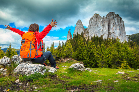 Young hiker carefree happy woman with backpack enjoying the freedom and the wonderful nature, Piatra Singuratica, Carpathians, Transylvania, Romania, Europe 写真素材
