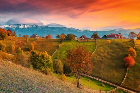 Beau paysage alpin d'automne, célèbre village alpin avec de superbes nuages colorés et de hautes montagnes enneigées en arrière-plan près de Bran, village de Magura, Transylvanie, Roumanie, Europe