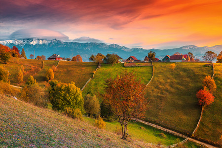 Beautiful autumn alpine landscape, famous alpine village with stunning colorful clouds and high snowy mountains in background near Bran, Magura village, Transylvania, Romania, Europe 免版税图像 - 106735244