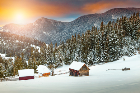 Spectacular Christmas winter landscape. Stunning colorful winter sunset, old rural mountain wooden chalets and snowy forest with pine trees near Brasov, Transylvania, Romania, Europe