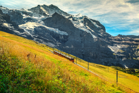 Wonderful Swiss landscape, famous electric red tourist train coming down from the Jungfraujoch station(top of Europe) in Kleine Scheidegg, Bernese Oberland, Switzerland, Europe Reklamní fotografie