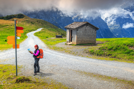 Summer holiday in mountains. Hiker woman with backpack, mountain equipment, paper map, orientate and find direction in mountains, Grindelwald, Bernese Oberland, Switzerland, Europe Фото со стока
