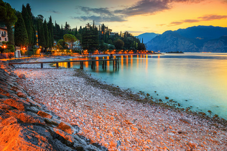 Fabulous place with stunning beach at sunset, Malcesine touristic recreation resort, lake Garda, Veneto region, Italy, Europe Standard-Bild